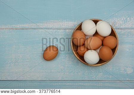 Close Up Wooden Bowl Of Brown And White Chicken Eggs On Light Blue Rustic Table Surface, Elevated To