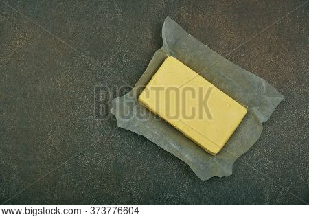 Close Up Open Fresh Yellow Hard Stick Butter In Paper On Grunge Table Surface, Elevated Top View, Di