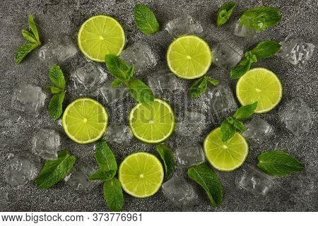 Close Up Flat Lay Of Lime Slices, Fresh Green Mint Leaves And Ice Cubes On Grunge Gray Stone Table S