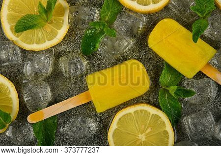 Close Up Frozen Juice And Limoncello Popsicles With Fresh Lemon Slices, Green Mint Leaves And Ice Cu