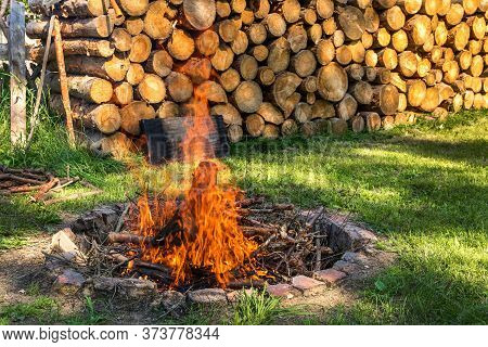 Outdoor Campfire Near A Pile Of Wood. A Place To Relax With Friends. Preparing For An Outdoor Barbec