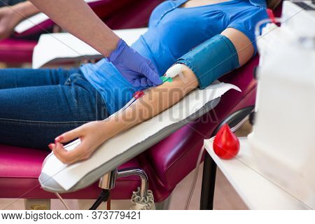 Young woman giving blood in a modern hospital (color toned image)