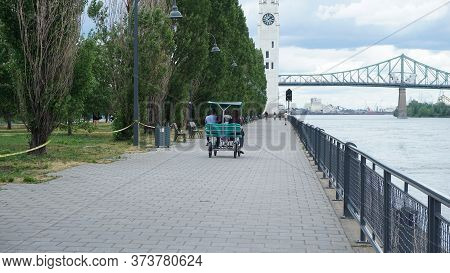 Montreal, Qc/ Canada - 6/25/2020: A Family Rides A Quadricycle At The Old Port After The Ease Of The