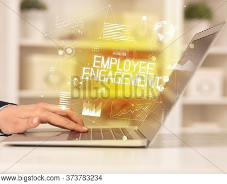 Side view of a business person working on laptop with EMPLOYEE ENGAGEMENT inscription, modern business concept