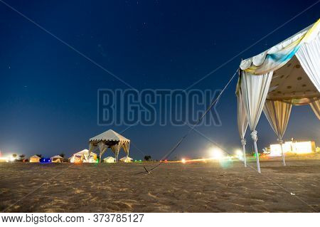 Night Shot Of Desert Camp In Sum In Thar Desert With White Tents For Visitors To Stay And The Blue S