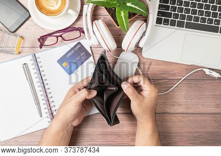 A Man Open Wallet Without Money On The Desk Consisting Of Credit Cards On Notebook,  Laptop Computer