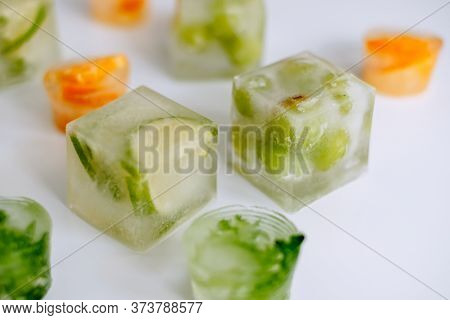 Frozen Fruits In Ice Cubes On A White Table. Close-up. High Quality Photo