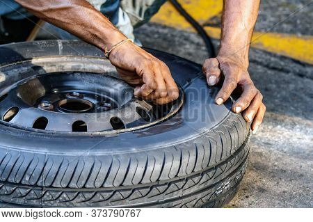 A Tyre Repairman Is Securing The Dust Cups On The Tyre Valve Outdoors In A Gas Station In Galle, Sri
