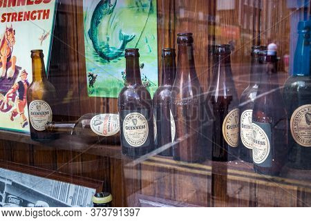 Dublin, Ireland - July 28, 2019: Group Of Guinness Old Glass Beer Bottles Placed On The Storefront O
