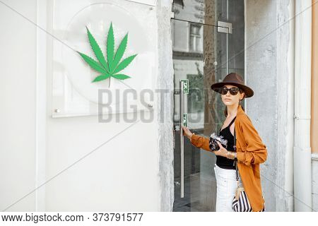 Woman Visiting Coffee Shop Or Store With Cannabis, While Traveling. Concept Of Legalization Of Marij