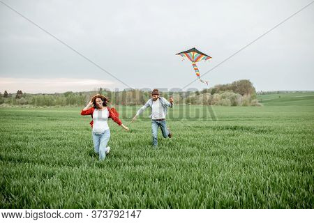 Happy Couple Having Fun Together, Playing With Kite On The Greenfield. Happy Couple Expecting A Baby