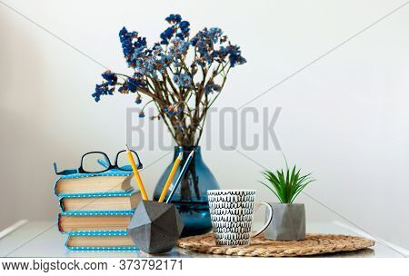 Cozy Home Interior Decor: Stack Of Books, Plants In Pots On A Wicker Stand, Vase With Flowers On A W