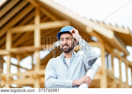 Portrait Of An Architect Or Builder In Hard Hat Standing In Front Of The Wooden House Structure. Bui
