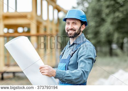 Portrait Of A Confident Builder In Blue Overalls And Hard Hat Standing With Blueprints On The Constr