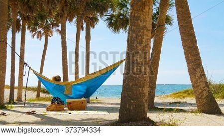 Romantic Couple Relaxing On Tropical Hammock. Young Man And Girl In Blue Hammock From Back In Beauti