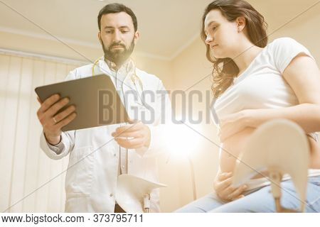 Doctor With Pregnant Woman During A Medical Consultation In Gynecological Office. Concept Of Medical