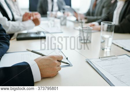 Hands of young elegant businessman in suit holding pencil over clipboard with contract or other document with colleagues on background