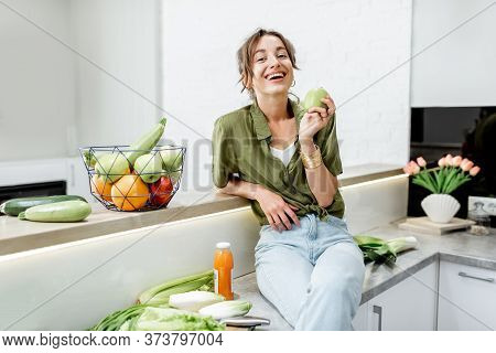 Portrait Of A Young And Cheerful Woman With Healthy Raw Food On The Kitchen At Home. Vegetarianism,