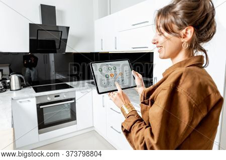 Young Woman Controlling Kitchen Appliances With A Digital Tablet, Mobile Device With Launched Smart