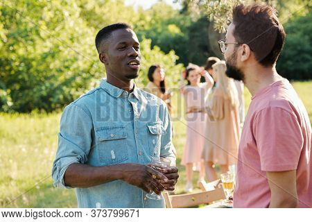 Young African man with glass of wine talking to mixed-race guy outdoors on background of their girlfriends having conversation