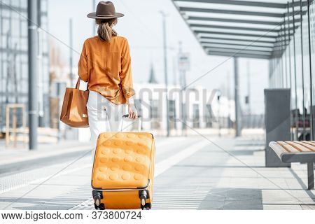 Young Female Traveler Walking With A Yellow Suitcase At The Modern Transport Stop Outdoors, Back Vie