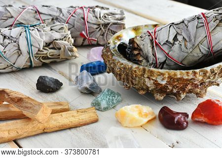A Close Up Image Of Rough Chakra Crystals And White Sage Bundles On A White Wooden Table.