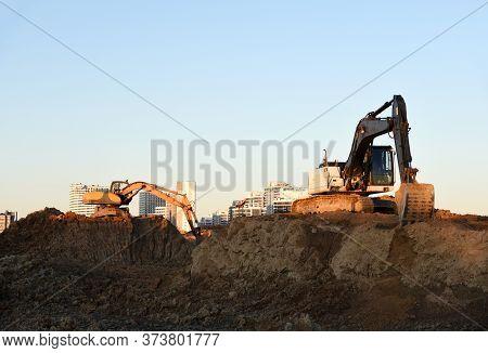 Excavator Working At Construction Site On Earthworks. Backhoe Digging Building Foundation. Paving Ou