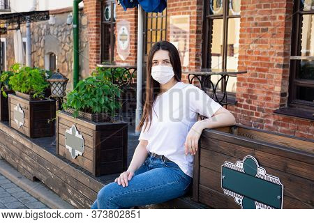 Сaucasian Young Woman In  Protective Mask On Her Face Is Sitting In Street Cafe. Looks At Camera. Po