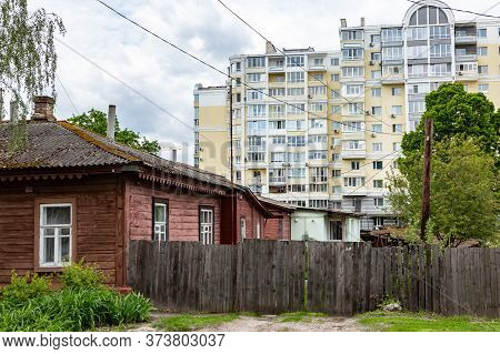 Old Wooden House With A Wooden Fence On The Background Of A Multi-storey New Building. Horizontal Or