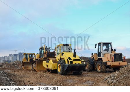 Soil Compactor, Bulldozer And Wheel Loader During The Construction Of Road At Construction Site. Hea