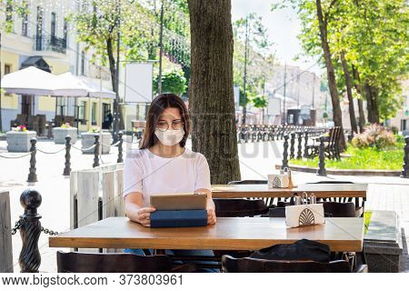 Caucasian Young Woman Protective Mask On Face Sitting In Cafe At Table. Works With Tablet. Concept: