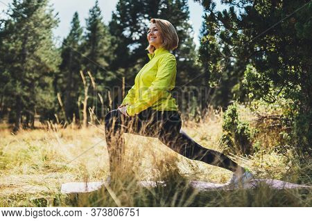 Fun Girl Exercising Outdoors In Summer Park, Activity With Stretch Legs. Smile Fitness Woman Stretch