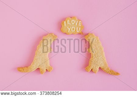 Homemade Shortbread Cookies With White Glaze On Pink Background, Top View. Two Dinosaurs With Callou
