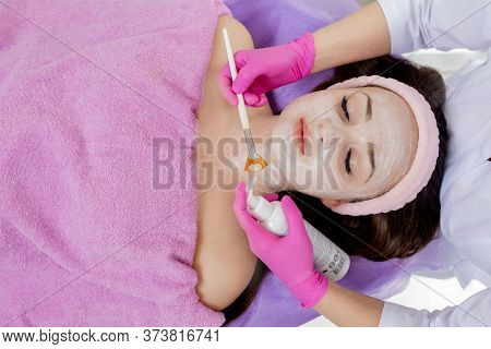 Beautician Makes A Face Clay Mask Against Acne On The Face Of A Woman To Rejuvenate The Skin. Cosmet