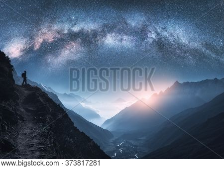 Arched Milky Way, Woman And Mountains At Night. Silhouette Of Standing Girl On The Mountain Peak, Mo