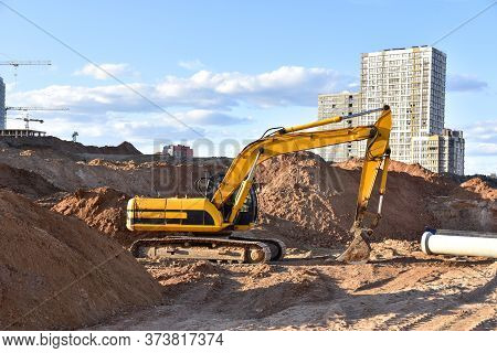 Excavator Working At Construction Site On Earthworks. Backhoe Digs Ground For Laying Concrete Sewage