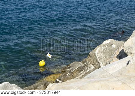 Rippled Aquamarine Sea Water And Small Yellow Buoy With Cypriot National Flag, View From Rocky Cliff