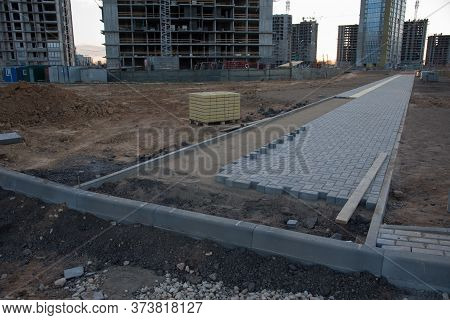Laying Paving Slabs At Construction Site. Process Of Installing Paving Bricks In The Town Pedestrian