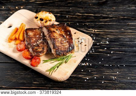 A Juicy Piece Of Fried Meat With Grilled Cherry Tomatoes Garlic And Carrot Lies On A Cutting Board A
