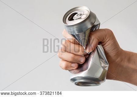 Male Hand Squeezes An Empty Aluminum Can For Recycling