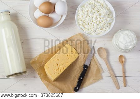 Fresh Milk, Cottage Cheese, Sour Cream And Cheese On Paper, As Well As Eggs In A Bowl Lie On A White