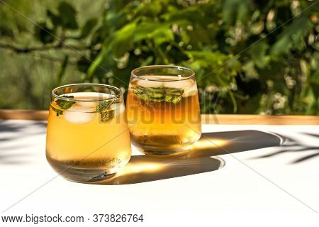 Iced Summer Drink. Two Glasses Of Refreshing Cold Green Tea With Mint Leaves And Ice Cubes On Summer