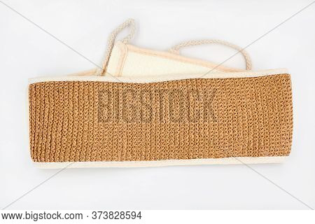 Natural Eco-friendly Jute Washcloth On A White Background. Brown Body Washcloth. Closeup, Top View