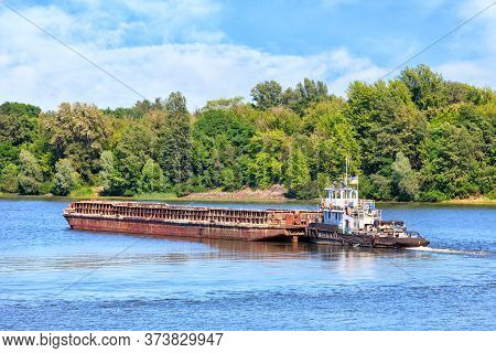 River Tugboat Pushes An Empty Rusty Barge Along The River Against The Background Of Coastal Greenery