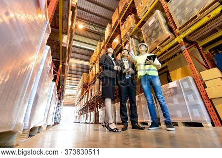 Portrait of engineer manager giving tour two businessman to inspect factory warehouse and discuss about warehouse inventory. Owner Investor Business deal and teamwork concept.