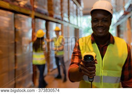Close up of african black woman warehouse worker hold hand scanner to check inventory stock in distribution warehouse. Traceability FIFO LIFO inventory just in time and warehouse concept photo.