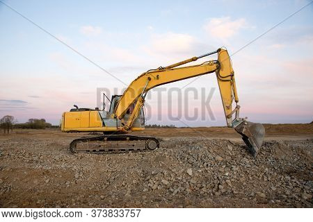 Excavator Working At Construction Site On Sunset Background. Backhoe Digs Gravel And Concrete Crushi