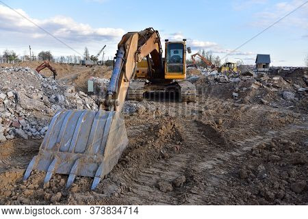 Excavator At Landfill For Work Concrete Demolition Waste. Salvaging And Recycling Construction Mater