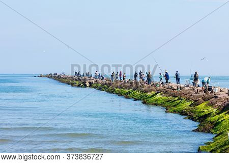 South Padre Island, Texas, Usa - November 19, 2019: People Fishing On A Breakwater At The Brazos San