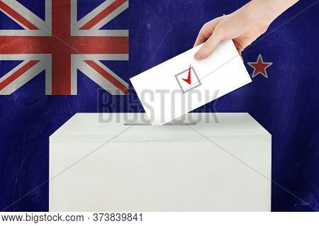 New Zealand Vote Concept. Voter Hand Holding Ballot Paper For Election Vote On Polling Station